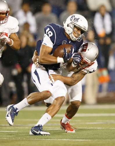 UNR's Wyatt Demps (19) gets tackled by UNLV's Peni Vea (42)